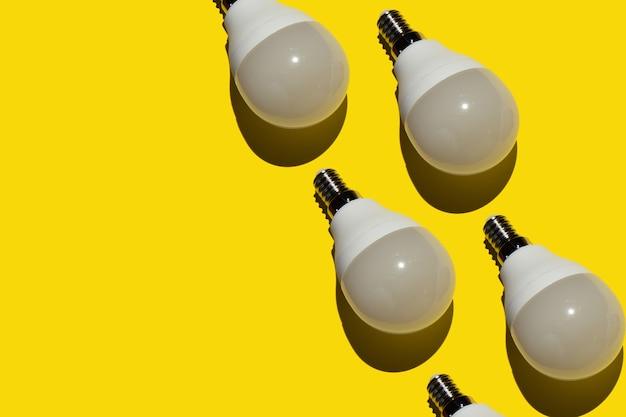 黄色の背景に多くの現代的な省エネ電球