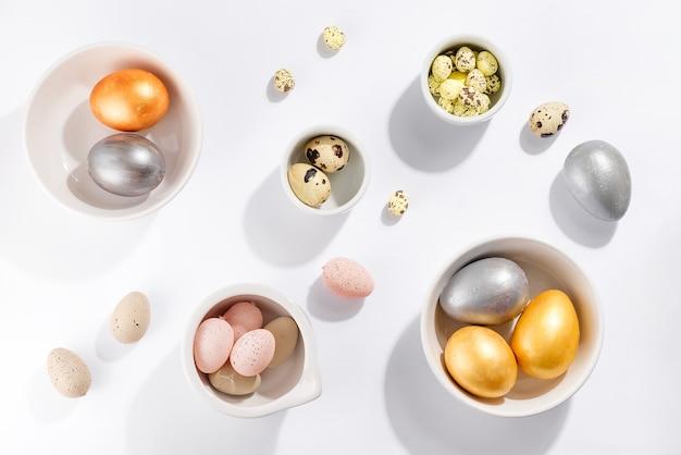 Много разноцветных пасхальных яиц в мисках разного размера на белом столе