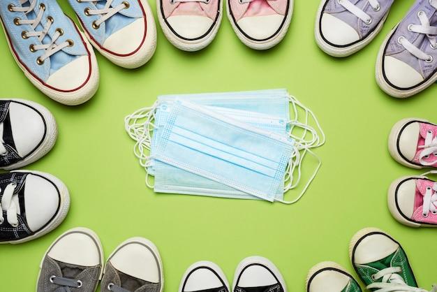 Множество разноцветных текстильных утомленных кроссовок разных размеров и стопка медицинских одноразовых масок