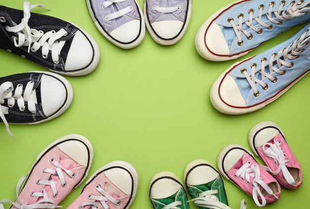 Много разноцветных потертых текстильных кроссовок разных размеров на зеленом фоне, вид сверху, концепция, семья и команда