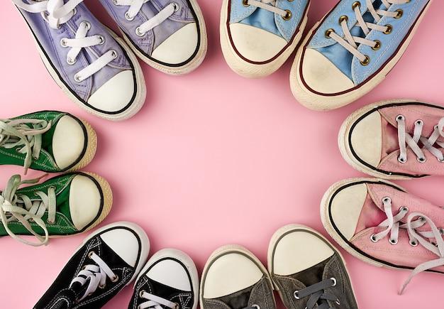 Много разноцветных потертых текстильных кроссовок разных размеров