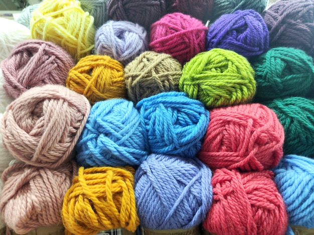 Many multi-colored wool skeins next to each other