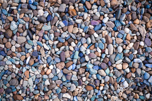 Many multicolor river pebbles top view