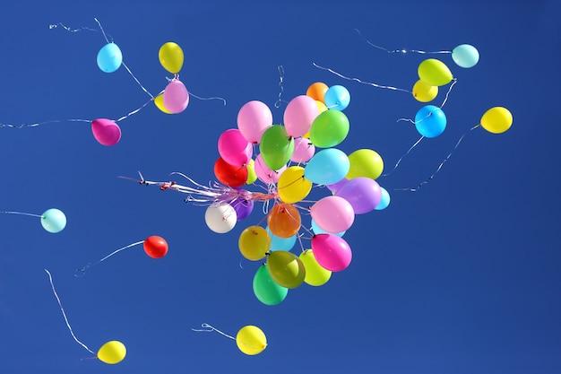 Многие разноцветные воздушные шары летают в голубом небе