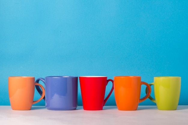 Many multicolored cups of coffee or tea on a blue background. the concept of a friendly company, a large family, meeting friends for a cup of tea or coffee.