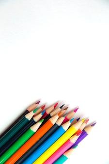 白い紙に多くの色とりどりの鉛筆。学校の準備ができています。