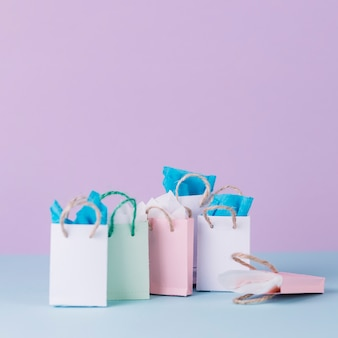 Many multicolored shopping paper bags in front of pink background