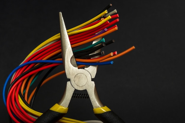 Many multicolored wires and round nose pliers