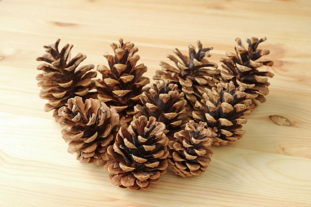 Many natural dry pine cones isolated on the light brown wooden table