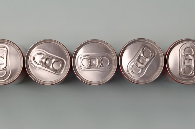 Many new aluminium cans of soda soft drink or energy drink containers. drinks manufacturing concept and mass production