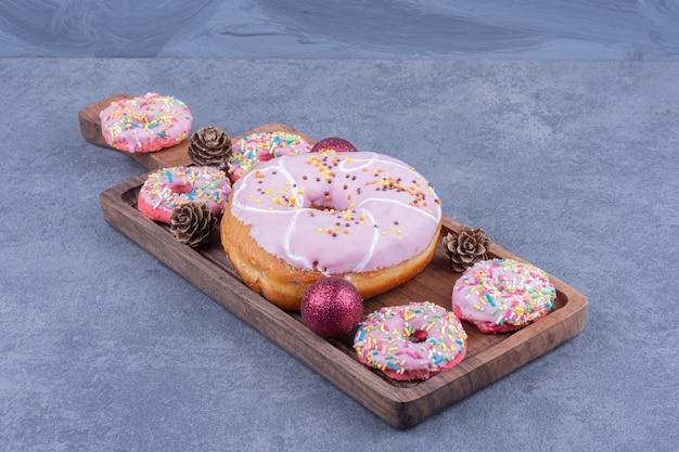 木の板に松ぼっくりのおいしいドーナツがたくさん