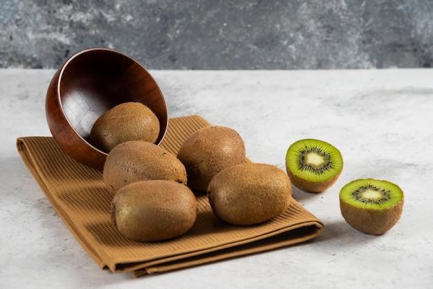 木製のボウルにおいしいキウイフルーツの多く