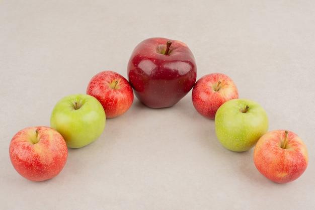白いテーブルの上のさまざまなリンゴの多く。