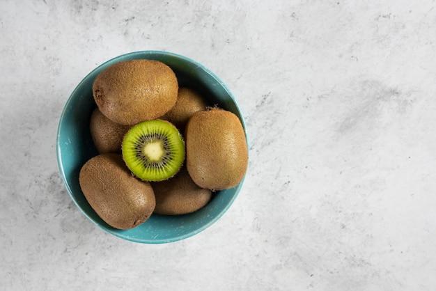 青いボウルに新鮮なキウイフルーツの多く。