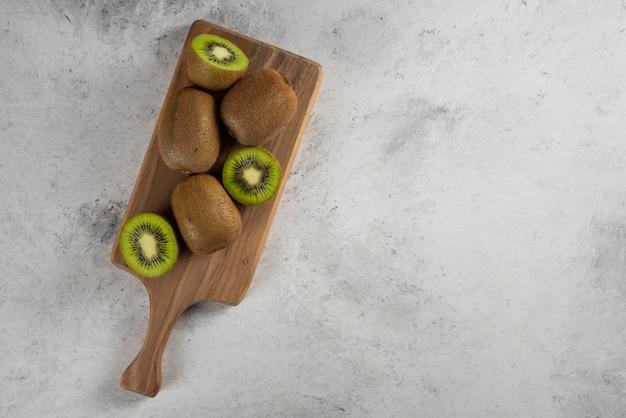 木の板に新鮮なキウイフルーツの多く。