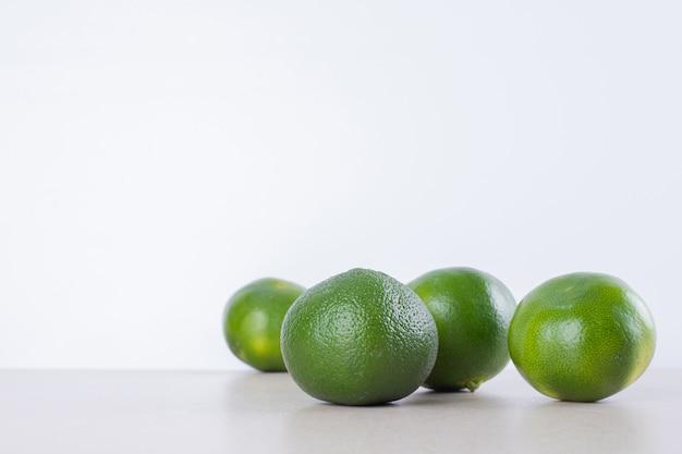 大理石の上の緑のタンジェリンの多く。