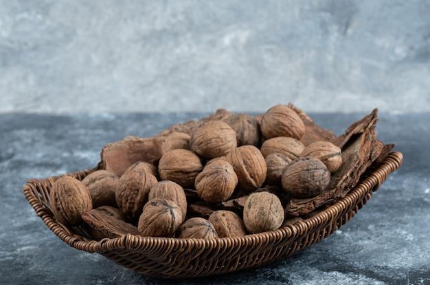 Много здоровых грецких орехов в плетеной корзине.