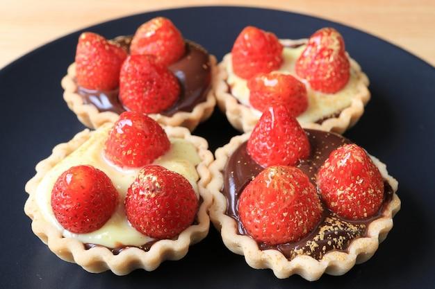 Многие из мини шоколадных пирогов с клубникой и порошком пищевого золота подаются на черной тарелке Premium Фотографии