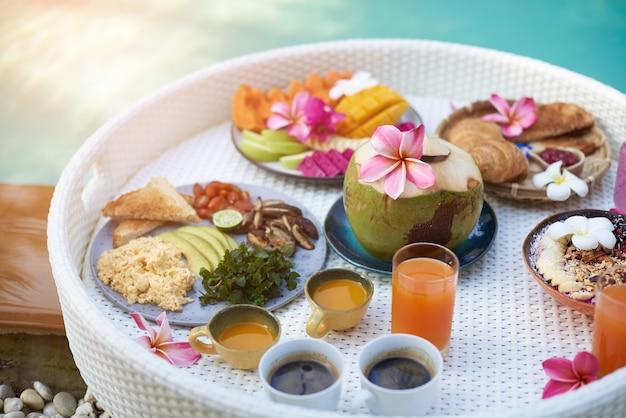 昼間のプールの周りの白いフローティングテーブルに自然で健康的なアジア料理の果物や飲み物の多く。