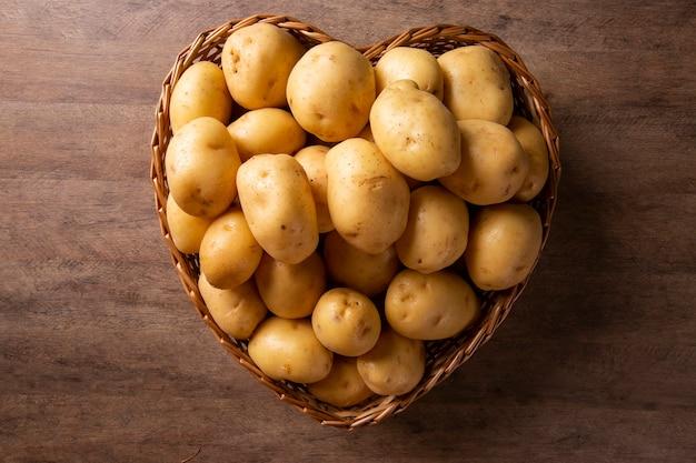 나무 표면에 심장 바구니에 감자의 많은.