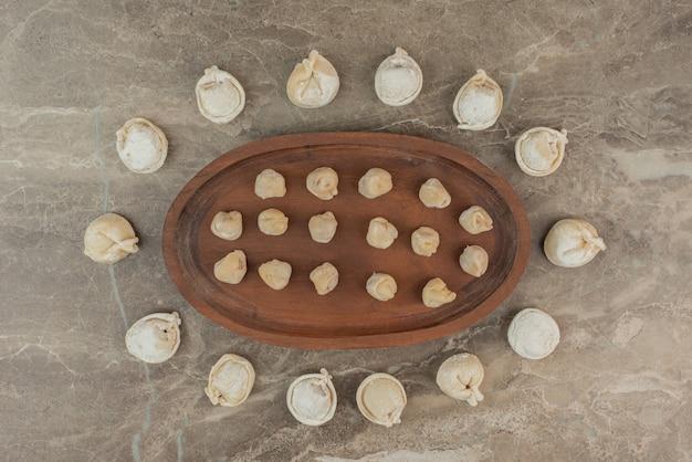 Многие из сырых пельменей на деревянной доске.