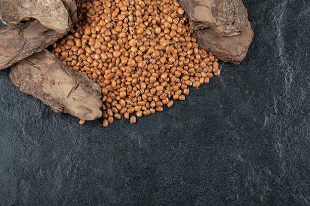 Многие из сырых коричневых фасолей на черном.