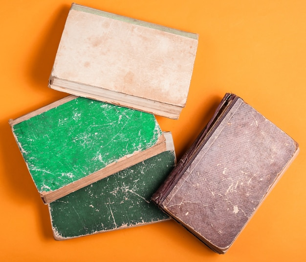 Many old book with shabby cover on orange background