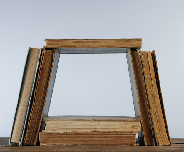 Many old books, smoking pipe on wooden shelf against the white wall