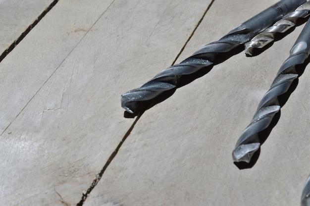 Многие старые сверла лежат на деревянной доске. крупный план.