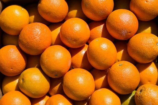 Many orange fruits at a market during sunny day.