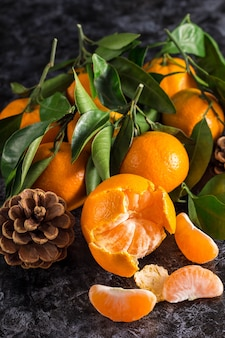 Many orange tangerines with green leaves on dark background. peeled mandarin slices and cones