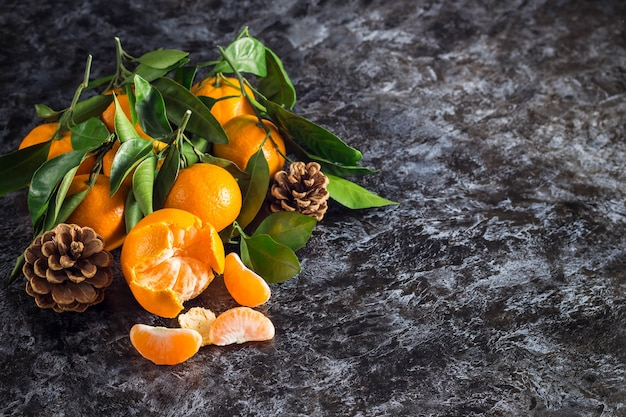 Many orange tangerines with green leaves on dark background with copy space. peeled mandarin slices and cones