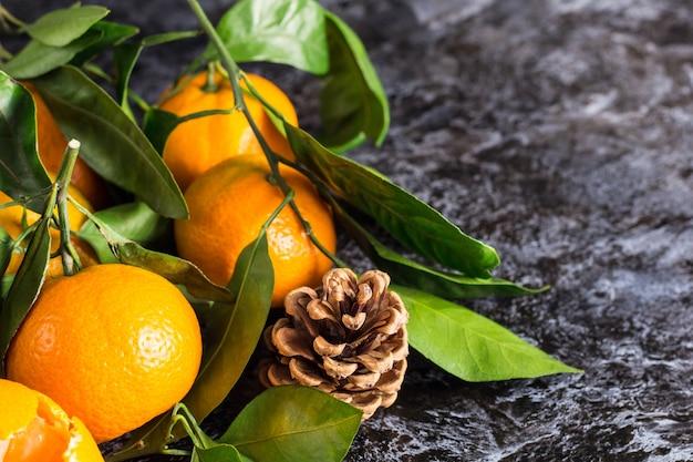 Многие оранжевые мандарины с зелеными листьями на темном фоне с копией пространства. очищенные дольки и шишки мандарина