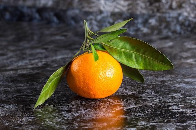 어두운 배경에 녹색 잎이 있는 많은 오렌지 귤