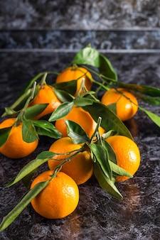 Многие оранжевые мандарины с зелеными листьями на темном