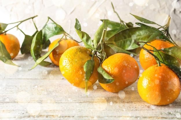 흰색 나무 배경에 녹색 잎이 있는 많은 오렌지 귤. 톤 보케와 눈
