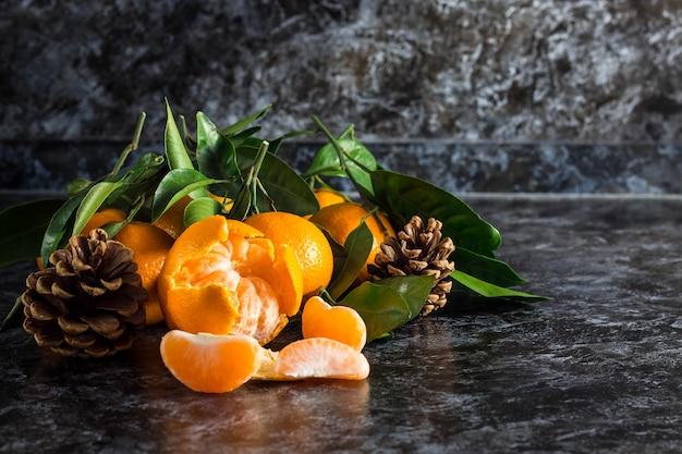 Много оранжевых мандаринов с зелеными листьями