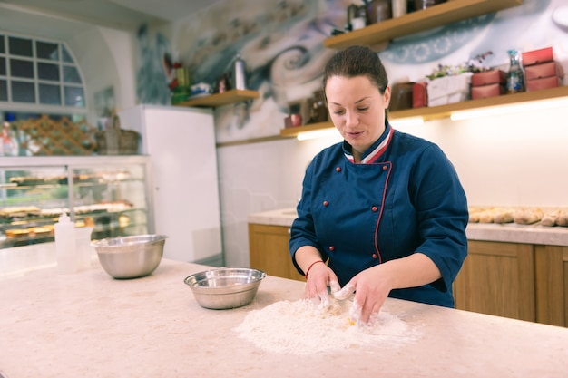 多くの注文。朝の注文が多すぎて時間に追われている黒髪の女性パン屋さん
