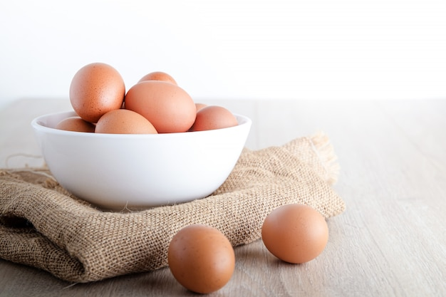 Many organic chicken eggs in a white bowl