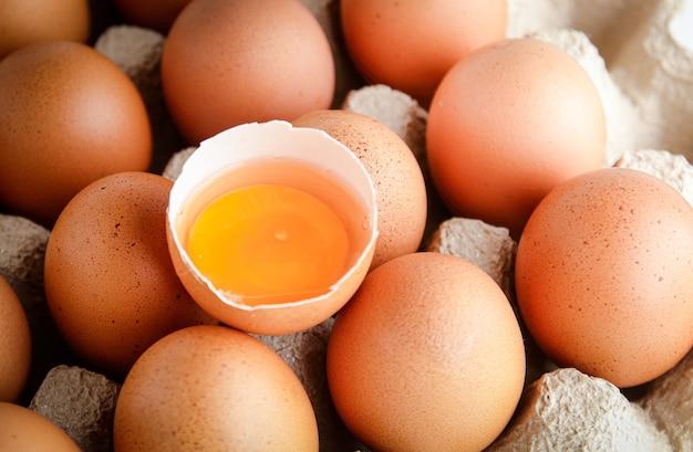 많은 유기농 계란을 종이 트레이에 넣고 중간에 계란 노른자가 있습니다. 몸에 이로운 음식이다.