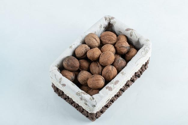 Many organic walnuts in wooden basket.