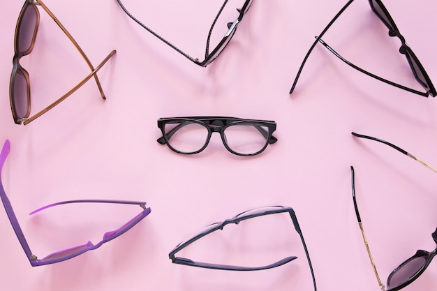 Many pairs of glasses on pink background