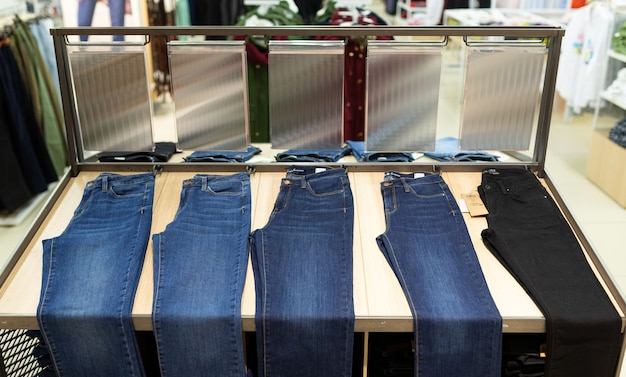 Many pants and jeans are hung in the department store