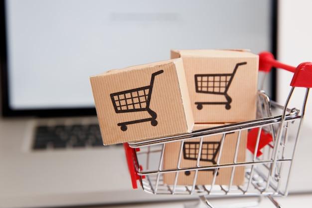 Многие бумажные коробки в небольшой тележке для покупок на клавиатуре ноутбука представляют собой концепцию покупок в интернете, когда потребители могут покупать вещи прямо из дома или офиса, просто используя несколько щелчков мышью через веб-браузер