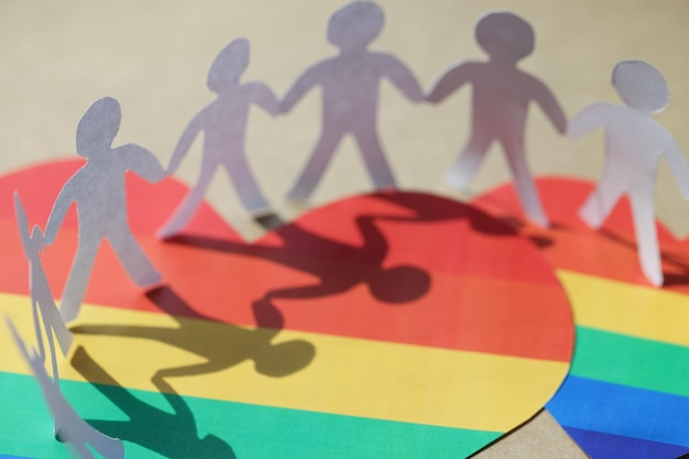 Many paper people standing on hearts with lgbt symbols closeup fight for rights of homosexuals