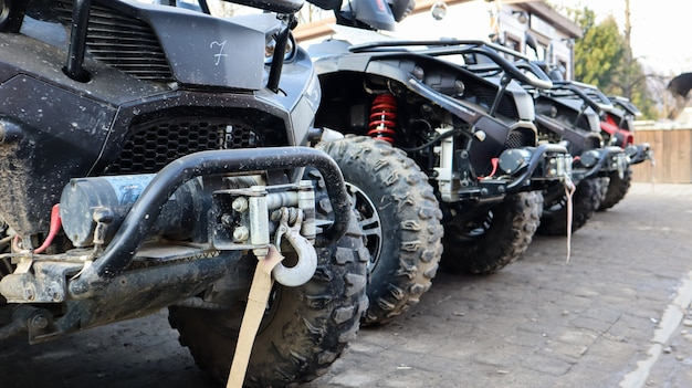 Many parked atvs on a dirt road, close up. four-wheel car, all-terrain vehicle. large wheels with powerful legs. mountain tour in the carpathians.