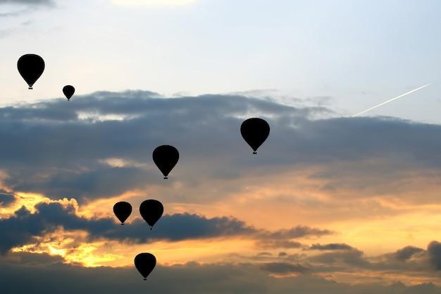 많은 승객 풍선이 구름에 새벽을 배경으로 날아갑니다.