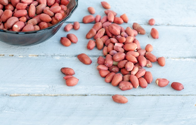 Many peanut kernels on a wooden table are gray-blue