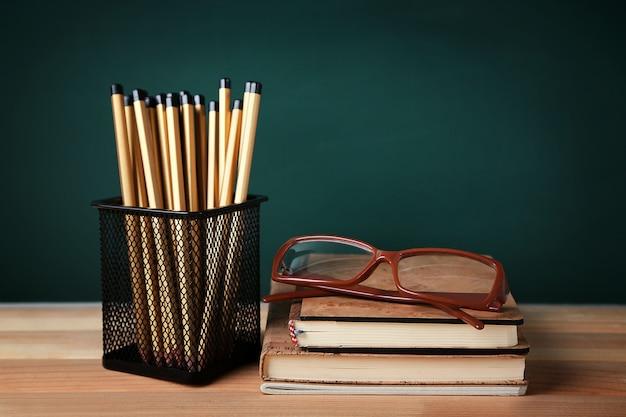 緑のボード上の木製のテーブルの金属ホルダーに多くの鉛筆