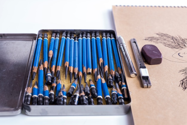 Many pencils used in the pencils box on the table